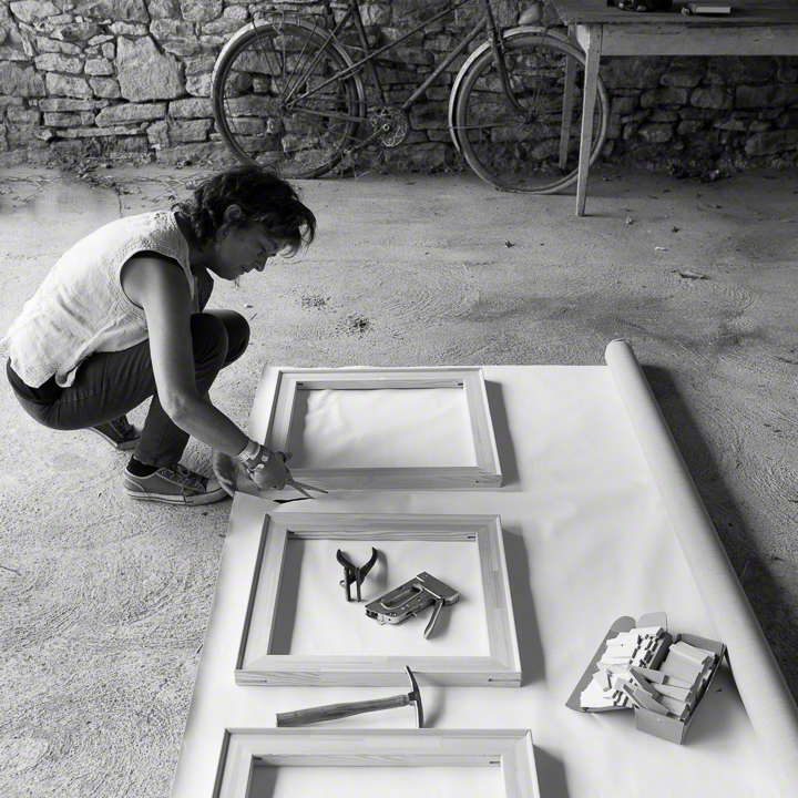 Woman, Catherine Forshall, crouching to cut canvas with scissors, on cement floor, using canvas stretcher as as template, stone wall, bicycle and table in background
