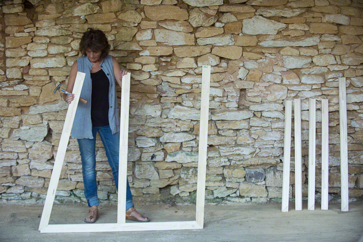 Woman in blue, Catherine Forshall, assembling stretchers, against background of stone wall