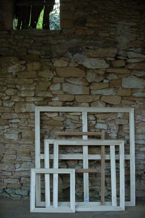 Wooden canvas stretchers against a stone wall